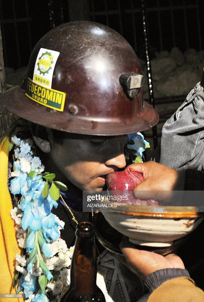 A Bolivian miner bites a raw llama heart during a 'wilancha' (sacrifice of animals) ritual to the Pachamama (Mother Earth) inside a shaft of the Hitos Nueva San Jose tin mine in the outskirts of Oruro, Bolivia, on February 8, 2013 during the miners carnival. AFP PHOTO/Aizar Raldes