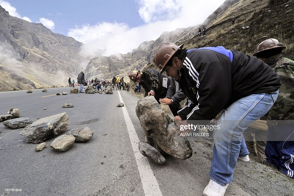 Bolivian miners associated in cooperatives block the road linking La Paz with Las Yungas near Pongo, 35 km northeast of La Paz, on September 25, 2012 during a protest demanding to the government the cession to their sector of the right of exploitation of the tin-rich Rosario seam. AFP PHOTO/Aizar Raldes