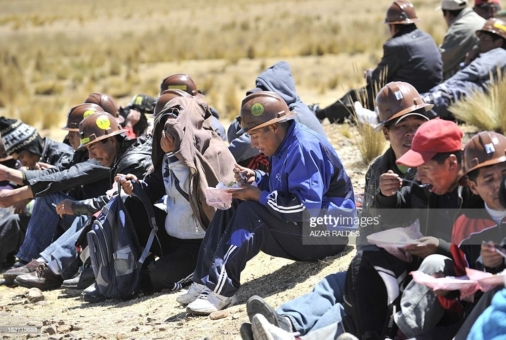 Bolivian miners associated in cooperatives blocking the road that leads to the border with Peru have a meal near Santa Ana, 90 km from La Paz, on September 24, 2012 demanding to the government the cession to their sector of the right of exploitation of the tin-rich Rosario seam. AFP PHOTO/Aizar Raldes