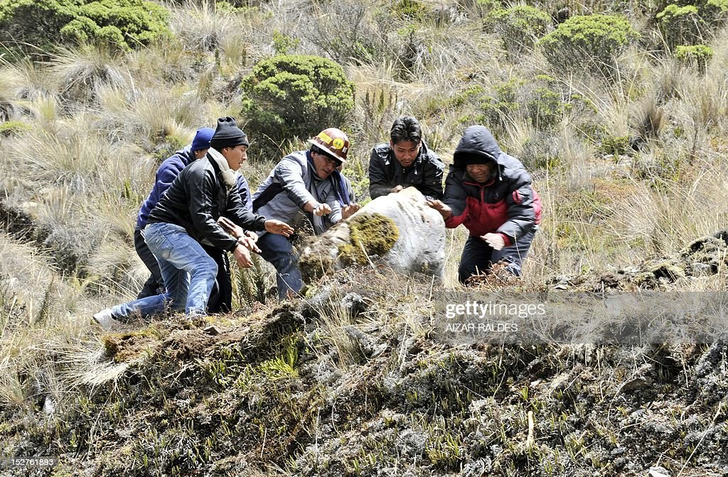 Bolivian miners associated in cooperatives move a rock to block the road linking La Paz with Las Yungas near Pongo, 35 km northeast of La Paz, on September 25, 2012 during a protest demanding to the government the cession to their sector of the right of exploitation of the tin-rich Rosario seam. AFP PHOTO/Aizar Raldes