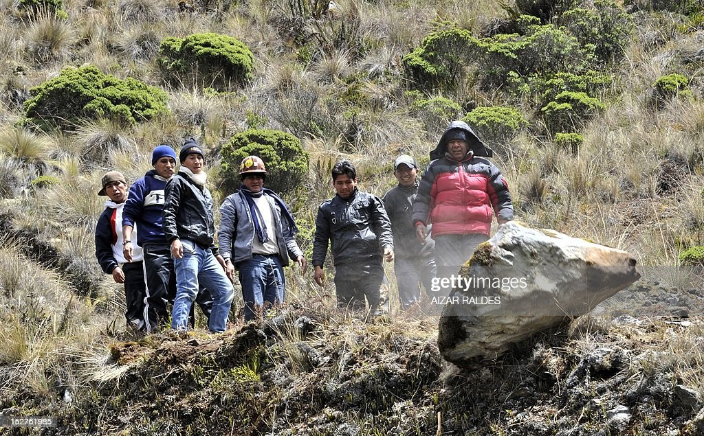 Bolivian miners associated in cooperatives move rocks to block the road linking La Paz with Las Yungas near Pongo, 35 km northeast of La Paz, on September 25, 2012 during a protest demanding to the government the cession to their sector of the right of exploitation of the tin-rich Rosario seam. AFP PHOTO/Aizar Raldes