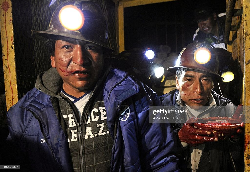 Bolivian miners carry a raw llama heart during a 'wilancha' (sacrifice of animals) ritual to the Pachamama (Mother Earth) inside a shaft of the Hitos Nueva San Jose tin mine in the outskirts of Oruro, Bolivia, on February 8, 2013 during the miners carnival. AFP PHOTO/Aizar Raldes