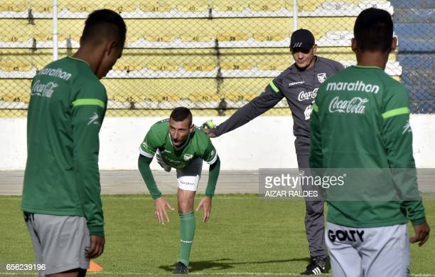 Bolivian national football player Pablo Escobar exercises next to team coach Mauricio Soria during a training session in La Paz on March 21 2017...