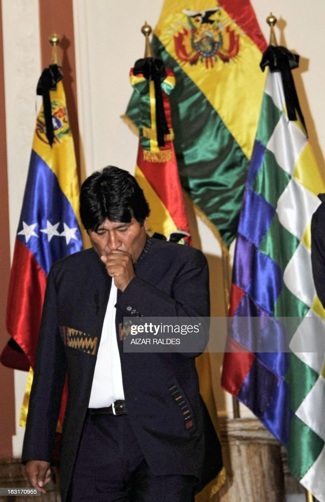 Bolivian President Evo Morales Ayma walks next to Bolivian and Venezuelan national flags at Quemado palace in La Paz before delivering a press conference to offer condolences after hearing of Venezuelan President Hugo Chavez's death on March 5, 2013. AFP PHOTO/Aizar Raldes
