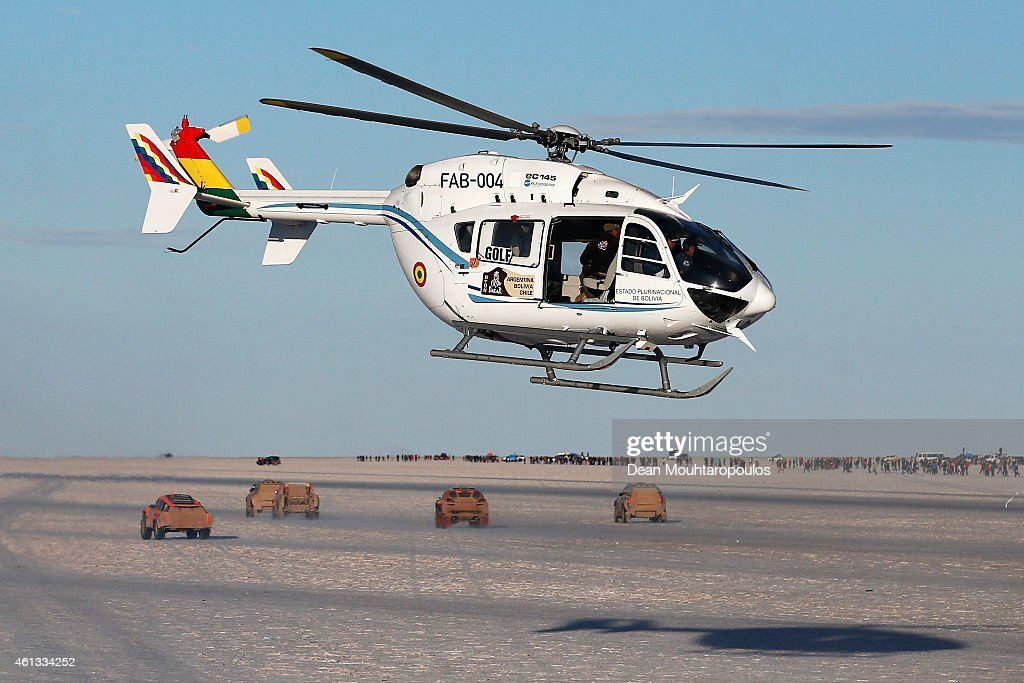 Bolivian President, <a gi-track='captionPersonalityLinkClicked' href=/galleries/search?phrase=Evo+Morales&family=editorial&specificpeople=272981 ng-click='$event.stopPropagation()'>Evo Morales</a> Ayma's helicopter flys above as cars #303, #301, #302,#308 and #310 start their race on day 8 of the Dakar Rallly on the Salar de Uyuni or Uyuni Salt Flats on January 11, 2015 in Uyuni, Bolivia.