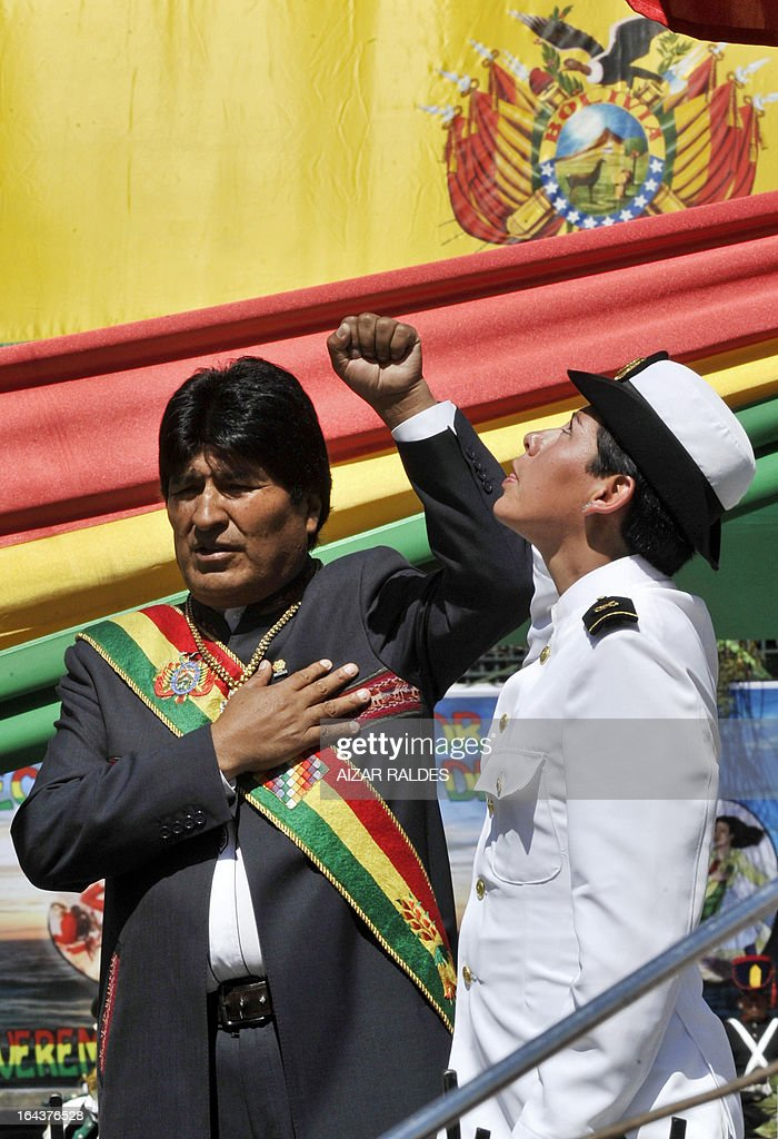 Bolivian President Evo Morales (L) sings the national anthem during a ceremony to commemorate the 134th anniversary of the Battle of Calama in which Bolivia lost its access to the sea to Chile, in La Paz on March 23, 2013. Morales said Saturday he would file a suit against Chile at the International Court of Justice 'in the coming days' in a bid to reclaim access to the sea lost in a 19th century war. During the event in honour of the 'Day of the Sea' -- commemorating the war that left impoverished Bolivia landlocked -- President Morales said he hoped to resolve the dispute through 'peaceful settlement mechanisms.' AFP PHOTO/AIZAR RALDES