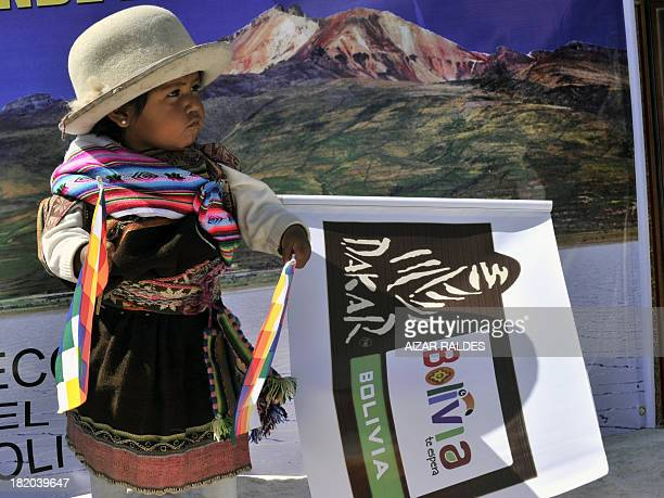 A Bolivian Quechua girl holds a promotional flag at the Salar de Uyuni southern Bolivia on September 27 2013 The Dakar Rally 2014 which kicks off on...
