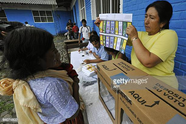 A Bolivian Quechua woman looks at a voting ballot before voting in the locality Villa 14 de Septiembre on December 6 2009 during presidential...