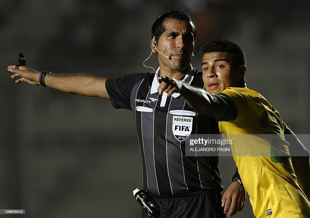 Bolivian referee Raul Orosco (L) and Brazilian Rafael Alcantara gesture during their South American U-20 Championship Group B football match against Venezuela, at Bicentenario stadium in San Juan, Argentina, on January 16, 2013. Four South American teams will qualify for the FIFA U-20 World Cup Turkey 2013. Brazil won by 1-0.