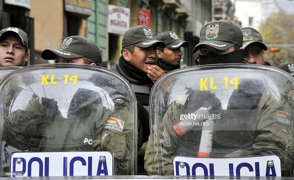 Bolivian riot policemen guard the surrouindings of the Plaza de Armas square, as workers demonstrate on the 12th day of an indefinite strike called by the Bolivian Workers' Central union (COB) to demand the government for a pension equivalent to 100% of their salaries, in La Paz on May 17, 2013. AFP PHOTO/Aizar Raldes