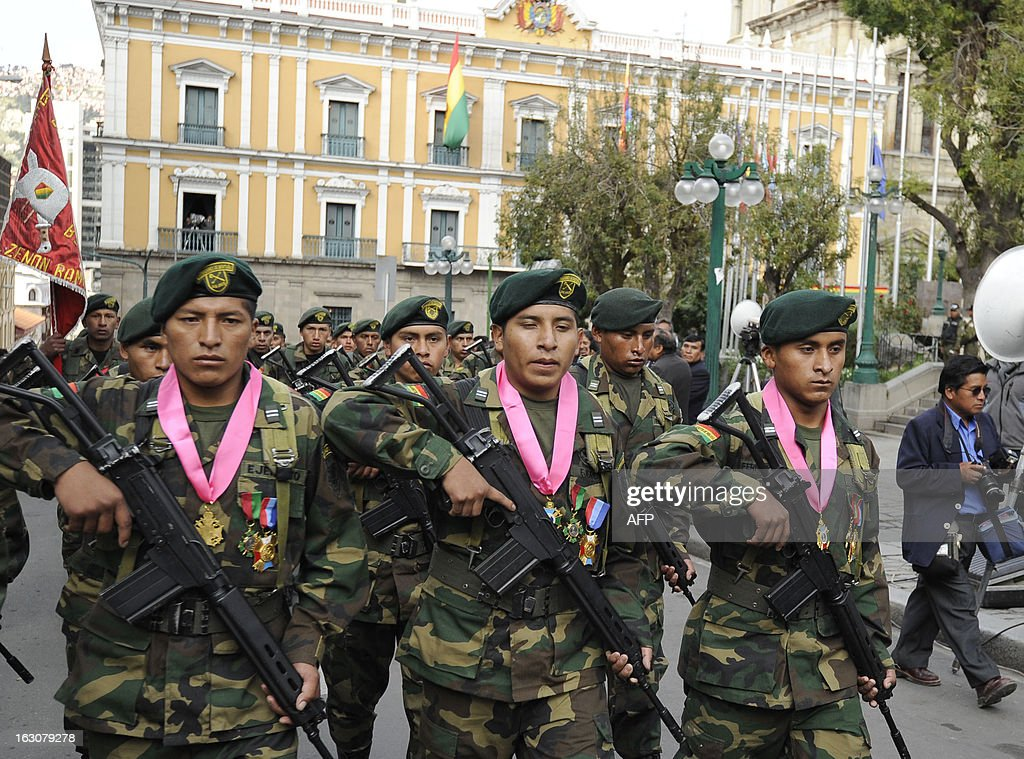 Bolivian soldiers Augusto Cardenas (L), Alex Choque (C) and Jose Luis Fernandez, who were arrested over a month ago in Chile after illegaly trespassing the border whilst in pursuit of car smugglers, parade with their unit after being decorated by Bolivian President Evo Morales, in front of the presidential palace Quemado in La Paz, on March 4, 2013. The three Bolivian soldiers, whose arrest in January had heightened the tense relations between the two South American neighbours, where welcomed in their country last week with military honours.