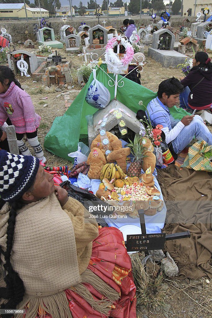 "Bolivian ""Tantawawa"" during the traditional celebration Feast of all Saints where families reunite in the cementery with the belief that the soul will visit the deceased relatives. They wait for them with a table full of flowers and tantawas (colorful bread with a mask) and drinks on November 02, 2012 in La Paz, Bolivia."