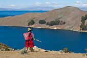 Bolivian woman with lake and hills