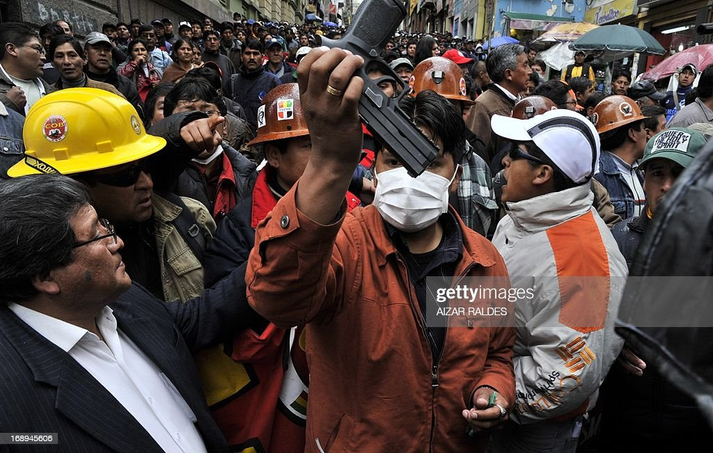 Bolivian workers shows a gun stolen to a plain clothes policeman during a protest on the 12th day of an indefinite strike called by the Bolivian Workers' Central union (COB) to demand the government for a pension equivalent to 100% of their salaries, in La Paz on May 17, 2013. AFP PHOTO/Aizar Raldes