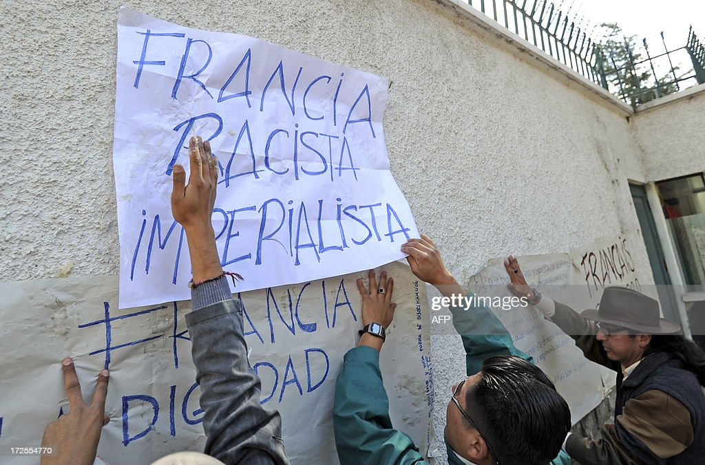 Bolivians hang placards with texts of protest on the exterior wall of the French embassy in La Paz on June 3, 2013. Bolivian officials accused France, Portugal, Italy and Spain of denying entry to the jet late Tuesday over 'unfounded rumors' Snowden was traveling on board. The placard they are handling reads 'France-Racist-Imperialist'.