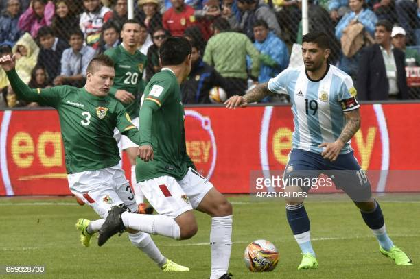 Bolivia's Alejandro Chumacero prepares to shoot against Argentina's Ever Banega during their 2018 FIFA World Cup qualifier football match in La Paz...