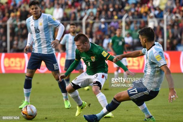 Bolivia's Alejandro Chumacero vies for the ball with Argentina's Marcos Rojo and Argentina's Matias Caruzzo during their 2018 FIFA World Cup...