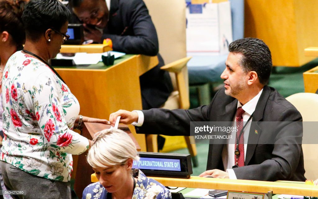 Bolivia's ambassador to the UN, Sacha Llorentis (R)casts his vote during the Election of five non-permanent members of the Security Council at the general assembly hall at the United Nations in New York on June 28 2016. / AFP / KENA