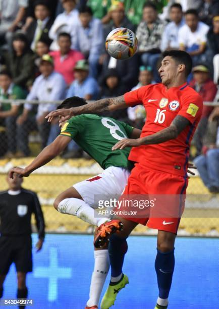 Bolivia's Diego Bejarano and Chile's Pedro Pablo Hernandez jump for a header during their 2018 World Cup qualifier football match in La Paz on...