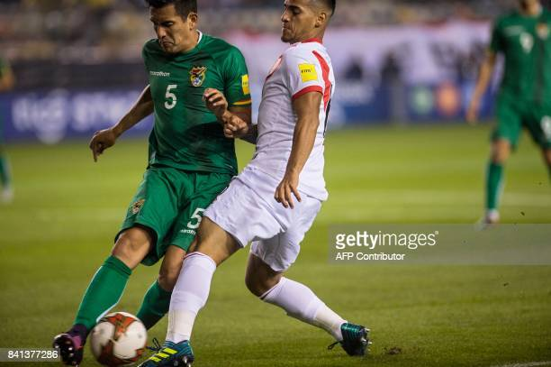 Bolivia's Gabriel Valverde is marked by Peru's Miguel Trauco during their 2018 World Cup qualifier football match in Lima on August 31 2017 / AFP...