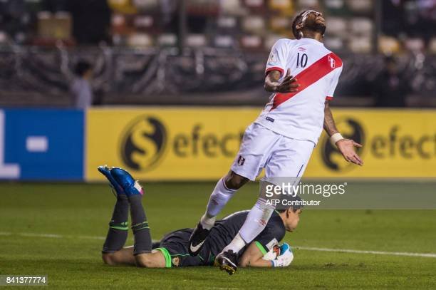 Bolivia's goalkeeper Carlos Lampe grabs the ball as Peru's Jefferson Farfan gestures during their 2018 World Cup qualifier football match in Lima on...