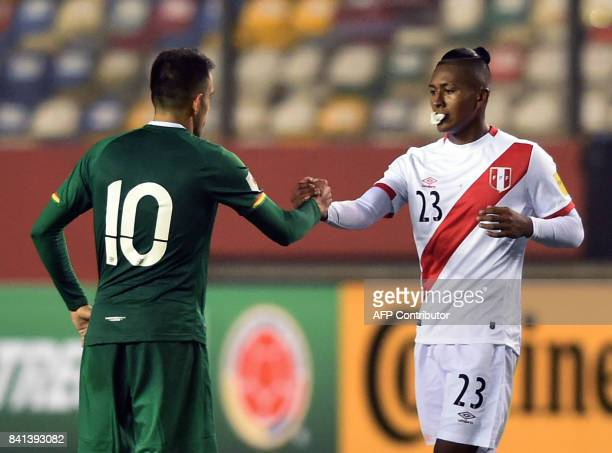 Bolivia's Jhasmany Campos and Peru's Pedro Aquino greet each other at the end of their 2018 World Cup football qualifier match in Lima on August 31...