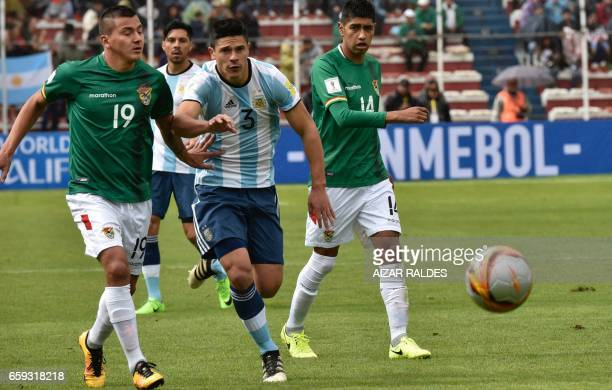 Bolivia's Jorge Flores and Raul Castro vie for the ball with Bolivia's Alejandro Chumacero during their 2018 FIFA World Cup qualifier football match...