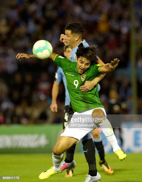 Bolivia's Marcelo Martins and Uruguay's Jose Maria Gimenez vie for the ball during their 2018 World Cup football qualifier match in Montevideo on...