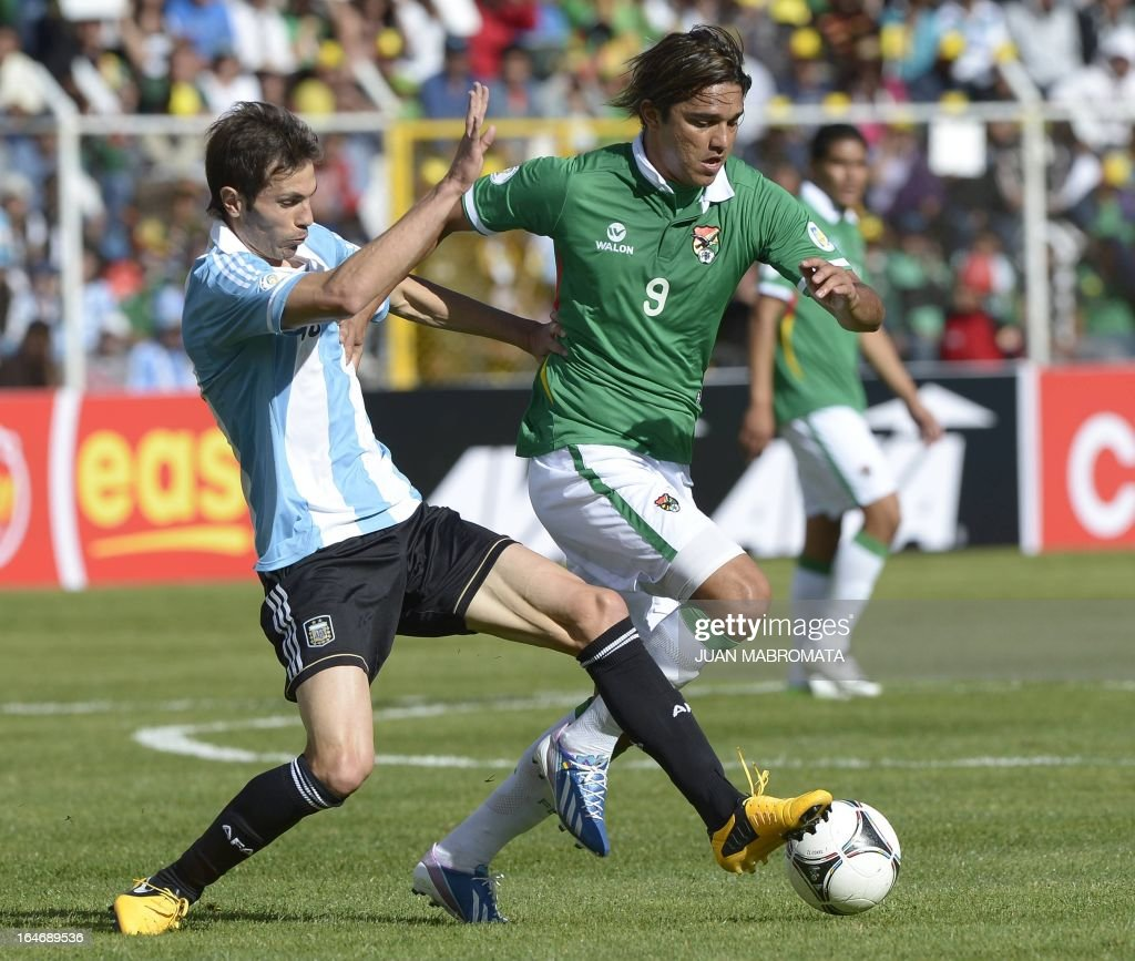 Bolivia's Marcelo Moreno Martins drives the ball as Argentina's Jose Maria Basanta during their Brazil 2014 FIFA World Cup South American qualifier...