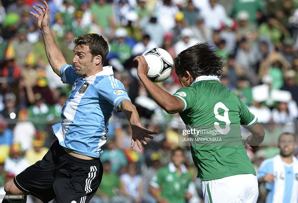 Bolivia's Marcelo Moreno Martins (R) heads the ball to score past Argentina's Hugo Campagnaro during their Brazil 2014 FIFA World Cup South American qualifier football match, at the Hernando Siles stadium in La Paz, on March 26, 2013. AFP PHOTO / JUAN MABROMATA
