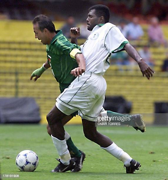 Bolivia's Oscar Sanchez is tackled by Saudi Arabia's Ibrahim Al Harbi 27 July 1999 during their Confederation Cup match at Azteca Stadium in Mexico...
