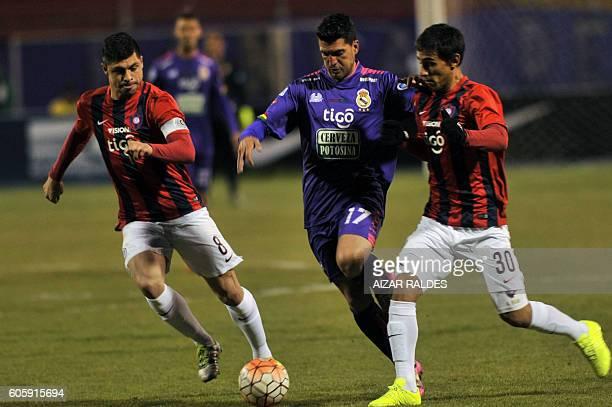 Bolivia's Real Potosi Ruben de la Cuesta vies for the ball with Paraguay's Cerro Porteño players Matias Rojas and Rodrigo Rojas during their Copa...