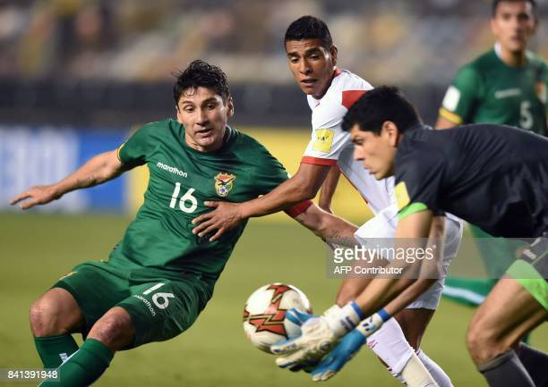 Bolivia's Ronald Raldes vies with Peru's Paolo Hurtado as Bolivia's goalkeeper Carlos Lampe catches the ball during their 2018 World Cup qualifier...