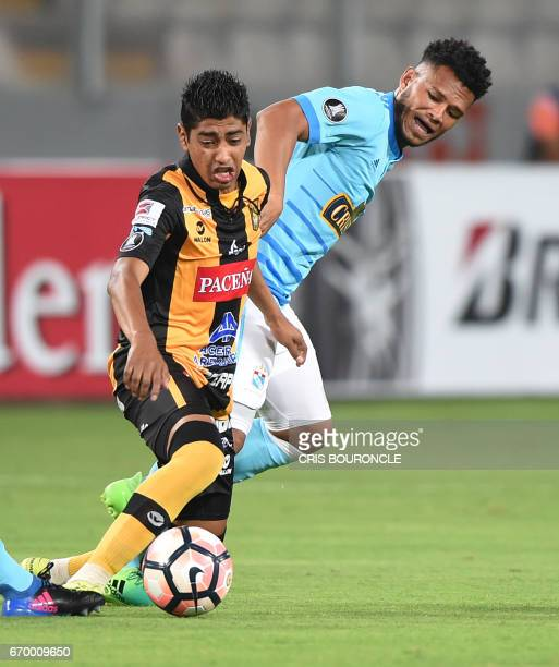 Bolivias Strongest player Raul Castro vies for the ball with Peru's Sporting Cristal Rolando Blackburn during their Copa Libertadores match at the...
