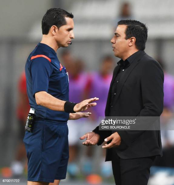 Bolivias The Strongest coach Cesar Farias is restrained from talking to players by the fourth umpire Paraguayan Julio Quintana during their Copa...