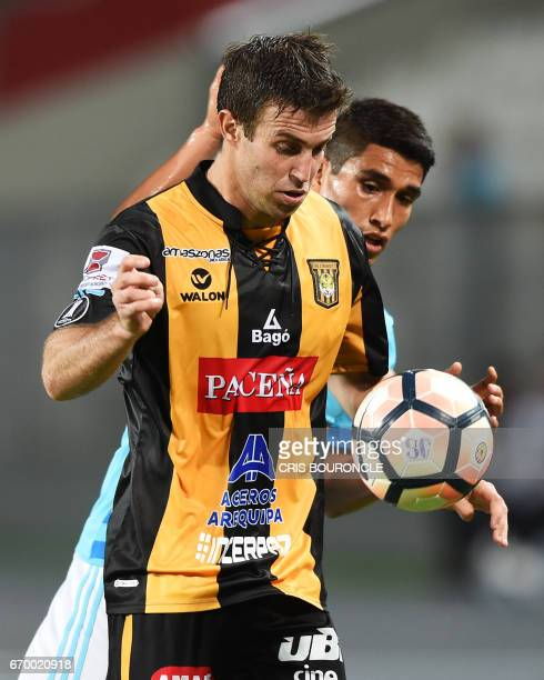 Bolivias The Strongest player Matias Alonso vies for the ball with Peru's Sporting Cristal player Irven Avila during their Copa Libertadores match at...