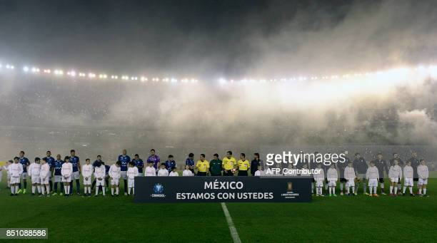 Bolivia's Wilstermann and Argentina's River Plate football teams pose behind a banner reading 'Mexico we are with you' before the start of their Copa...