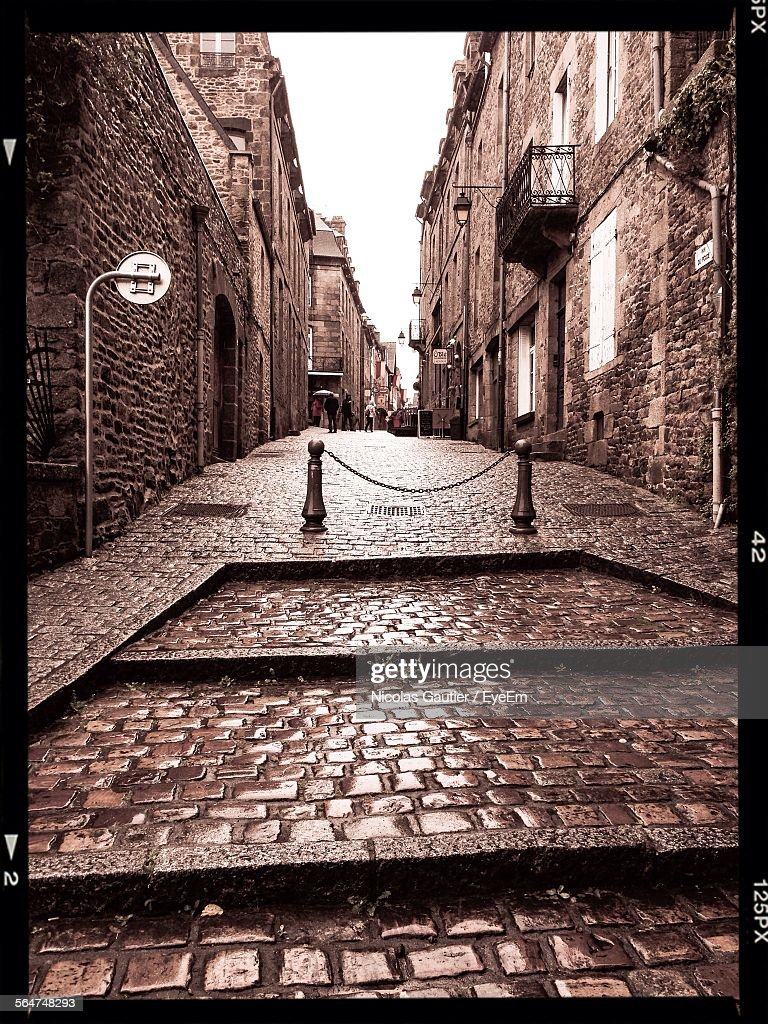 Bollard In Front Of Cobbled Alleyway Of Old City