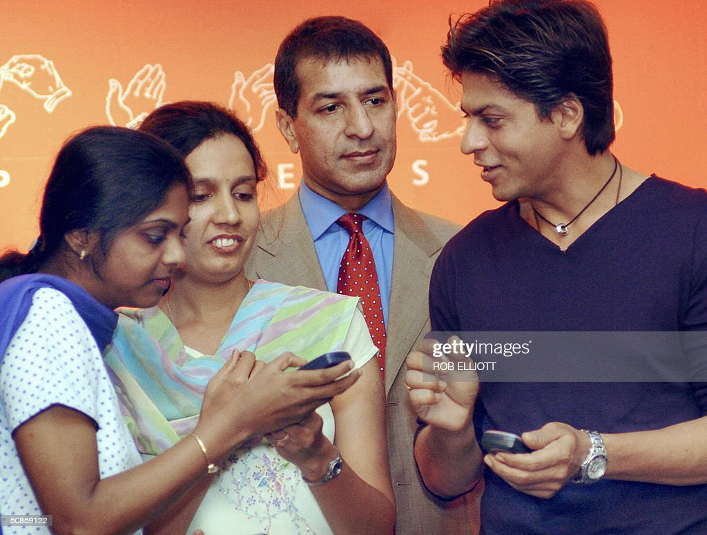 Bollywood actor and AirTel Brand Ambassador, Shahrukh Khan (R) checks with hearing impaired, Kavita Pethe (2nd L) and watched on by Joint Managing Director Bharti Teli-Ventures, Rajan Bharti Mittal (2nd R) to see if she received an SMS message from Khan during a press conference in Bombay, 20 May 2004, to launch AirTel and Bharti Tele -Ventures Ltd joint 'confidence plan'. The 'confidence plan' entails a slew of benefits such as 2000 free AirTel to AirTel SMS's within the local network along with the facility to send SMS to other local, national and international networks. In essence, the 'confidence plan' envisages giving highly subsidized SMS to facilitate communication within the hearing impaired community. Girl at left unidentified. AFP PHOTO/Rob ELLIOTT