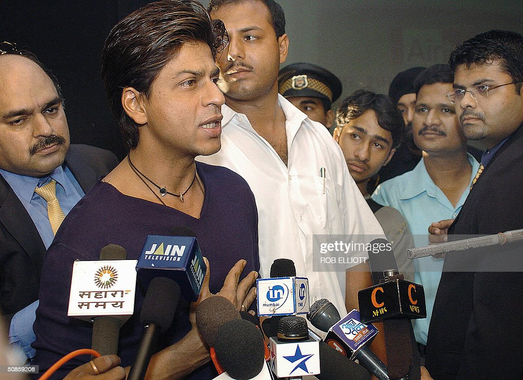 Bollywood actor and AirTel Brand Ambassador, Shahrukh Khan (2nd L) gives an interview after a press conference in Bombay, 20 May 2004, to launch AirTel and Bharti Tele -Ventures Ltd joint 'confidence plan'. The 'confidence plan' entails a slew of benefits such as 2000 free AirTel to AirTel SMS's within the local network along with the facility to send SMS to other local, national and international networks. In essence, the 'confidence plan' envisages giving highly subsidized SMS to facilitate communication within the hearing impaired community. AFP PHOTO/Rob ELLIOTT
