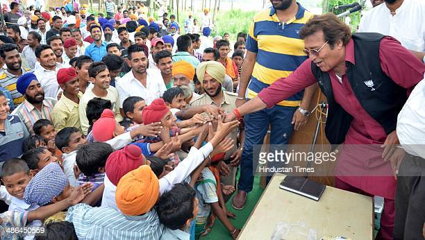 Bollywood actor and BJP Lok Sabha Candidate from Gurdaspur Vinod Khanna greets supporters during a public meeting for election campaign at Saroopwali...
