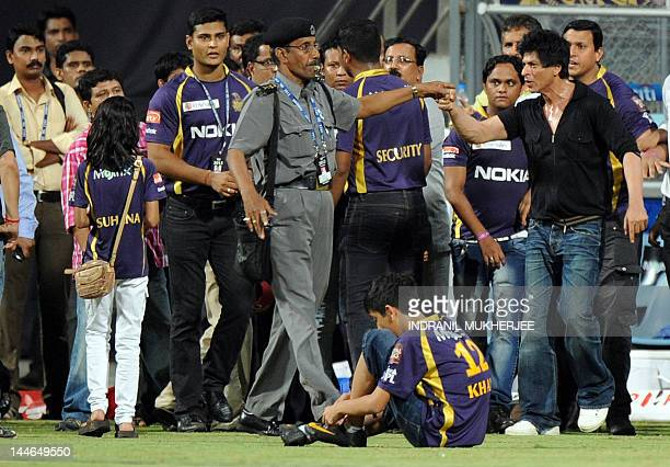 Bollywood actor and Indian Premier League franchise Kolkata Knight Riders coowner Shah Rukh Khan is watched by his daughter Suhana as he gestures...