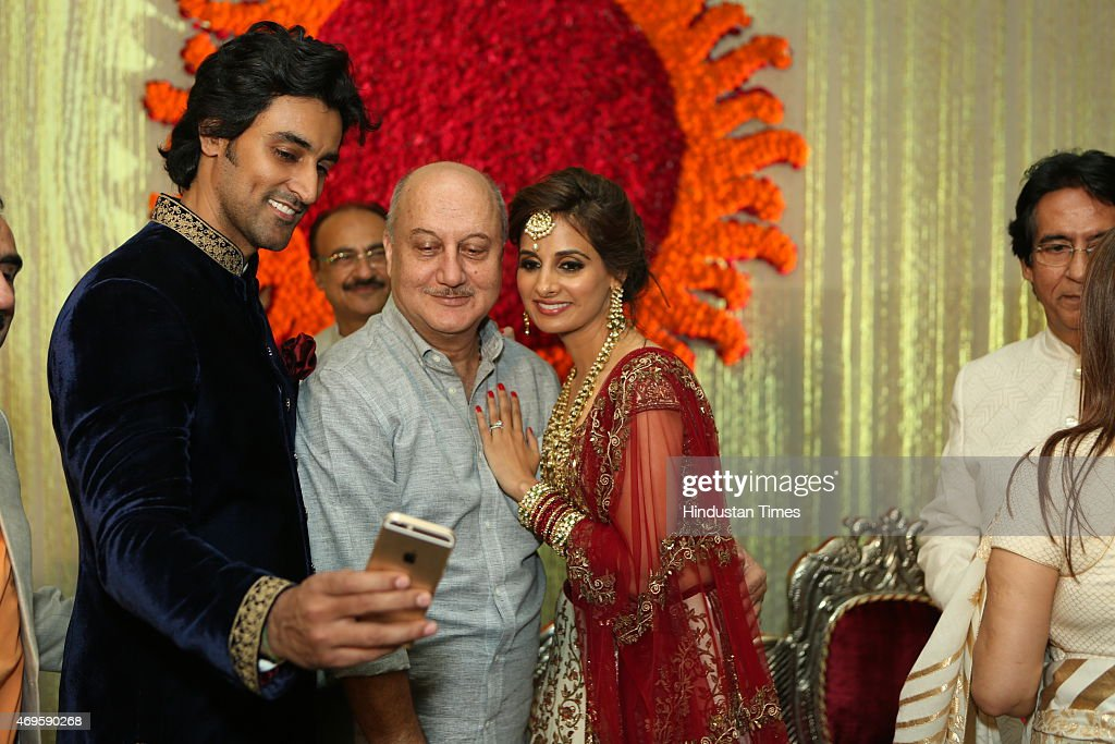 Bollywood actor Anupam Kher having a selfie with newlywed couple Kunal Kapoor and Naina Bachchan during their wedding reception on April 11 2015 in...