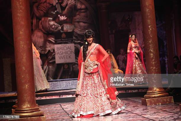 Bollywood actor Chitrangada Singh walked the ramp in a red and gold shimmery lehenga for Indian fashion designer Suneet Varma on Day 5 at Indian...