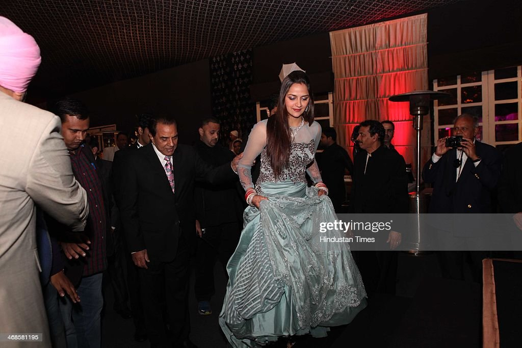Bollywood actor Dharmendra escorting his daughter Ahana Deol during reception of her weddibg with Vaibhav Vohra on February 5, 2014 in New Delhi, India. Ahana, a budding Odissi dancer, is the daughter of Bollywood stars Dharmendra and Hema Malini while Vaibhav in an Indian businessman. They married on February 2, 2014 in Mumbai.
