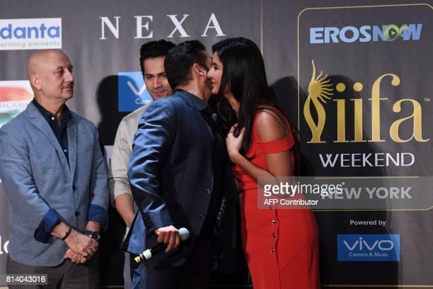 Bollywood actor Salman Khan greets actress Katrina Kaif as Anupam Kher and Varun Dhawan look on during a press conference ahead of the 18th...