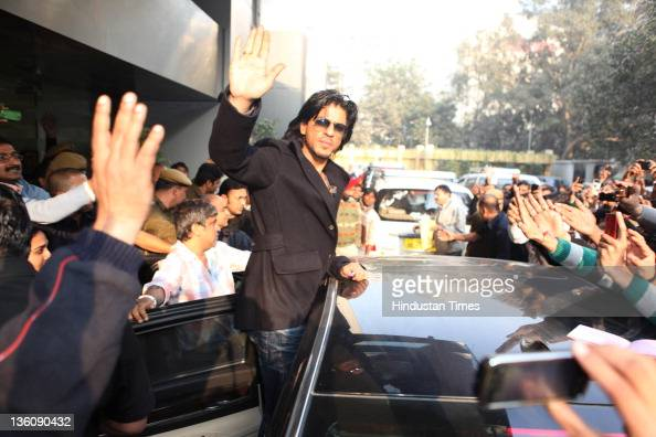 Bollywood actor Shahrukh Khan waving hand at cheering fans on his arrival at Hindustan Times house on December 19 2011 in New Delhi India The...