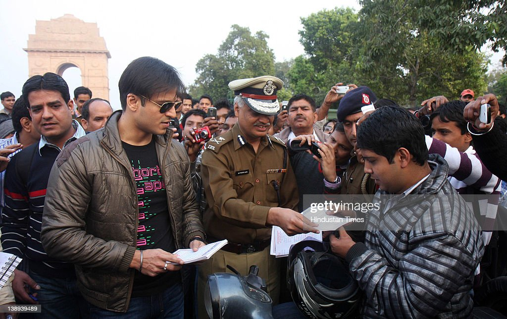 Bollywood actor <a gi-track='captionPersonalityLinkClicked' href=/galleries/search?phrase=Vivek+Oberoi&family=editorial&specificpeople=627274 ng-click='$event.stopPropagation()'>Vivek Oberoi</a> explains the need of wearing a helmet to a motor cyclist near India Gate on February 13, 2012 in New Delhi, India. Oberoi is in the city to shoot his film 'Kismet Love Paisa Dilli', and lent his support to the traffic police's 'Respect the Pedestrian' drive.