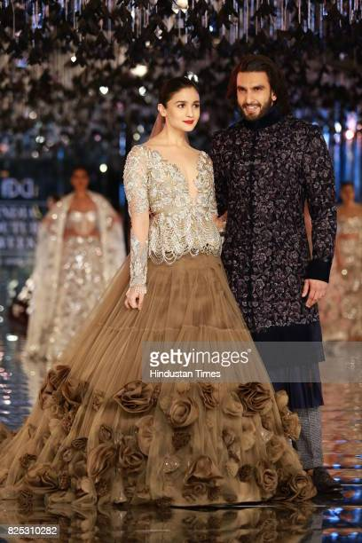Bollywood actors Alia Bhatt and Ranveer Singh walk on the ramp showing creations made by designer Manish Malhotra during the India Couture Week 2017...