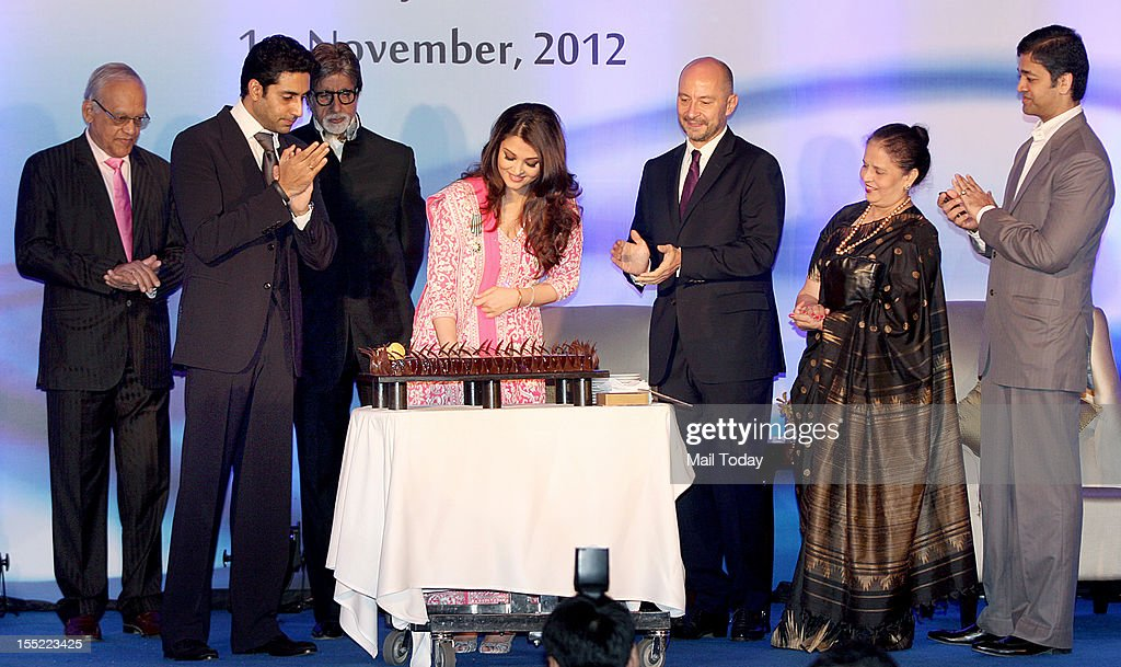 Bollywood actress Aishwarya Rai Bachchan cuts a cake on her birthday as her husband Abhishek Bachchan, father-in-law Amitabh Bachchan and French Ambassador to India, Francois Richier (R) applaud at a function in Mumbai on Thursday. Aishwarya was conferred with the French civilian award, Officer Dan Ordre Arts et des Lettres at the function.
